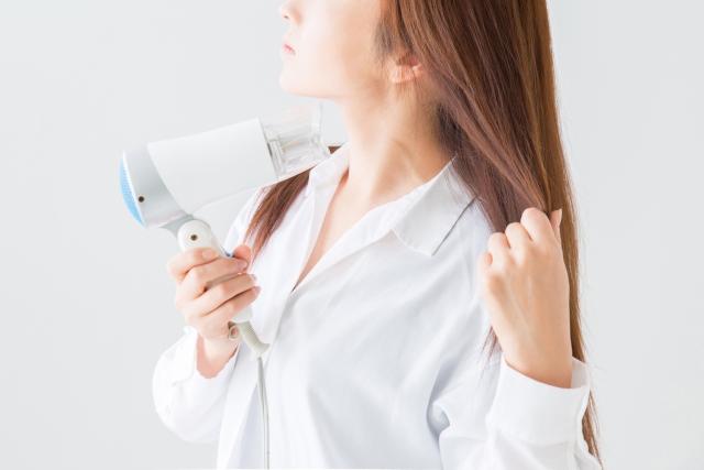 女性がドライヤーで髪を乾かしている写真